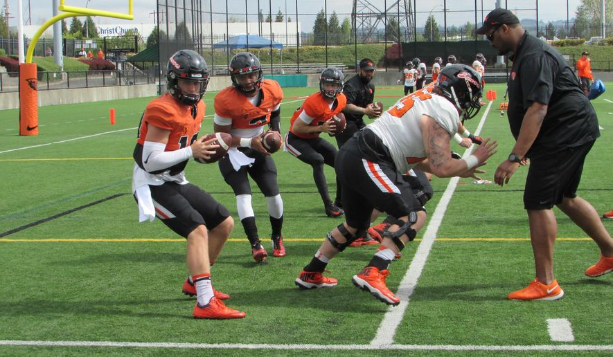 Oregon State quarterbacks Darell Garretson, left, and Marcus McMaryion practice during an spring NCAA college football training at Hillsboro Stadium in Hillsboro, Ore., Saturday, April 9, 2016. (AP Photo/Anne M. Peterson)
