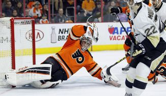 Philadelphia Flyers' Steve Mason, left, comes up with a save on a shot from Pittsburgh Penguins' Kael Mouillerat, right, during the first period of an NHL hockey game Saturday, April 9, 2016 in Philadelphia. (AP Photo/Tom Mihalek)