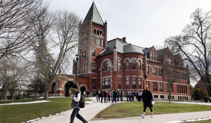 In this photo taken Wednesday April 6, 2016 students walk past the historic Thompson Hall at the University of New Hampshire in Durham, N.H. (AP Photo/Jim Cole)