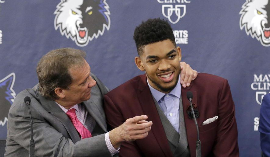FILE - In this June 26, 2015, file photo, Minnesota Timberwolves' Karl-Anthony Towns, right, the No. 1 overall pick in the NBA draft, shares a laugh with head coach Flip Saunders during an NBA basketball news conference in Minneapolis.  Towns has put together a historic rookie season that has him steamrolling toward the Rookie of the Year award. Before it all began, he had to endure the grief of losing NBA legend Darrell Dawkins, who Towns called Uncle Darrell, and Saunders, the coach who picked him No. 1. (AP Photo/Ann Heisenfelt)
