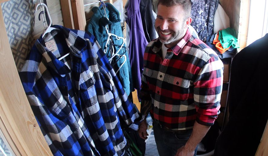 Advance For Saturday April 9 - In this Sunday, March 6, 2016, photograph, David Bowler shows off his closet in the interior of a tiny house on wheels located in Grand Junction, Colo. David Bowler and his wife, Shayla, are participating in a trend sweeping the nation called minimalism. (Christopher Tomlinson/The Grand Junction Daily Sentinel via AP) MANDATORY CREDIT
