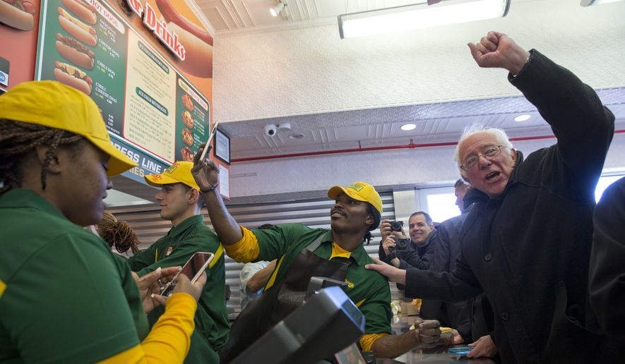 Democratic presidential candidate, Sen. Bernie Sanders, I-Vt., gestures to the crowd while ordering a hot dog at Nathans Famous in Coney Island in the Brooklyn borough of New York, Sunday, April 10, 2016. (AP Photo/Mary Altaffer)