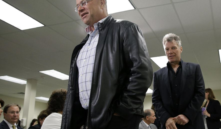 FILE - In this Tuesday, April 14, 2015 file photo, billionaire hedge fund manager David Tepper, left, and Rock and Roll star Jon Bon Jovi walk together at an event in Toms River, N.J. The spotlight turned to Tepper this week when legislative budget forecaster Frank Haines cited the billionaire's move to Florida as a potential factor in how much income tax revenue the state brings in. Income tax revenues make up the biggest share of cash in state coffers, and a shift in projections of as little as 1 percent amounts to about $100 million, forecasters say. (AP Photo/Mel Evans,file)