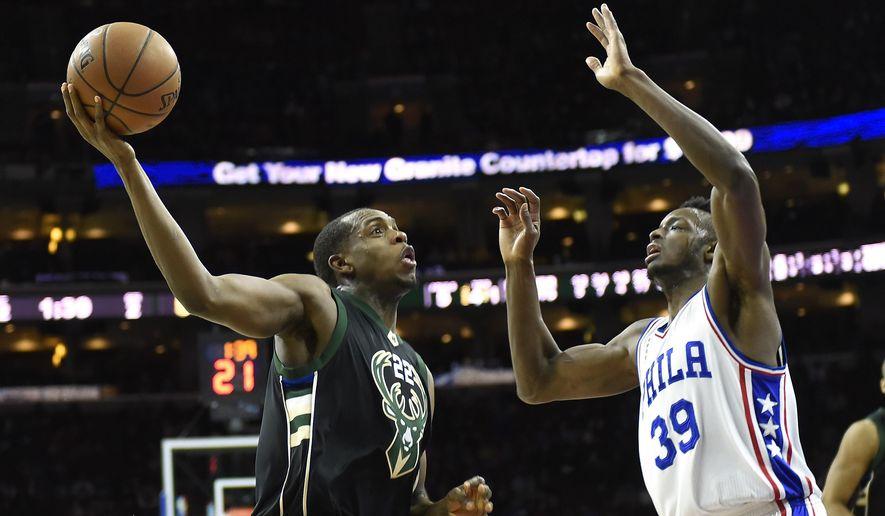 Milwaukee Bucks' Khris Middleton (22) drives to the basket as Philadelphia 76ers' Jerami Grant (39) defends during the first half of an NBA basketball game, Sunday, April 10, 2016, in Philadelphia. (AP Photo/Michael Perez)