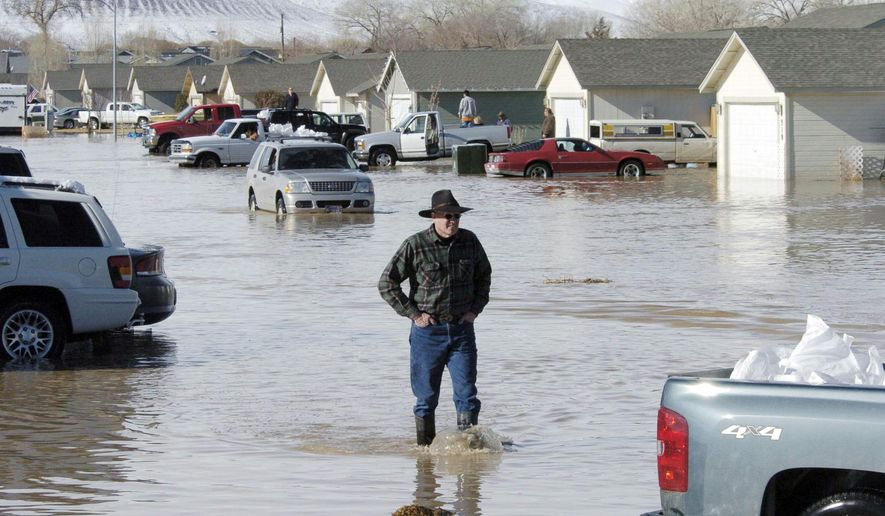 FILE -- In this Jan. 5, 2008 file photo, a man walks amid the flooded area in Fernley, Nev. Eight years, dozens of lawyers and hundreds of thousands of documents later, more than 200 Nevada flood victims are finally going to get paid for damages suffered when a century-old irrigation canal burst and sent a wall of water into their homes in 2008. (Tim Dunn/Reno-Gazette Journal via AP, File)