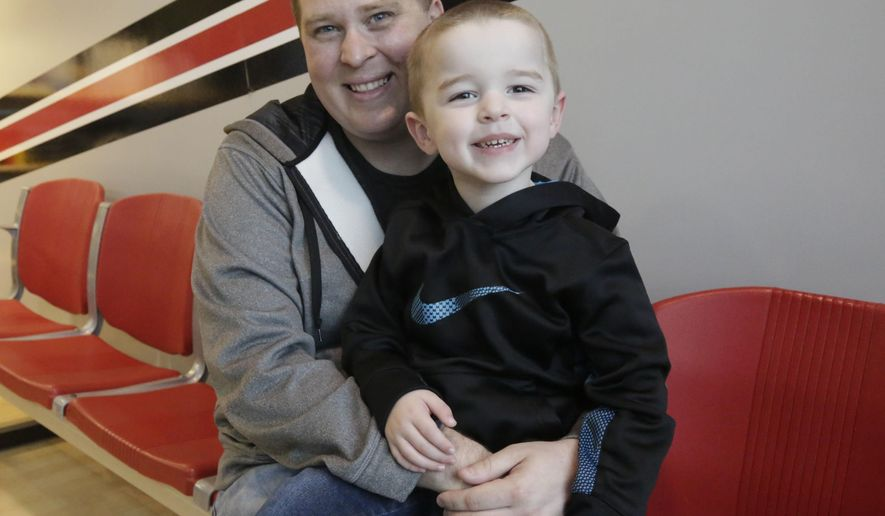 In this April 6, 2016, photo, Ed Izenstark and his son Chase, 4, pose in St. Charles, Ill. Izenstark inherited a genetic predisposition to Huntington's disease from his birth father, but he only learned of his susceptibility to the fatal nerve disorder after requesting information about his adoption from a state agency last December. Illinois state Rep. Sara Feigenholtz, D-Chicago, wants to make adoption records more transparent to help thousands of people across the state access more details about their family background. (AP Photo/M. Spencer Green)