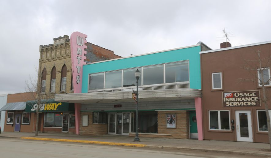 ADVANCE FOR USE SUNDAY, APRIL 10 - This photo taken March 14, 2016, shows the exterior of the Watts Theathre along Main Street in Osage, Iowa. The theater, with its neon lights, chrome, pink and teal facade, sticks out among the more subdued buildings on the street. (Arian Schuessler/Globe-Gazette via AP) MANDATORY CREDIT