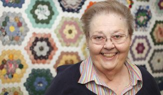 In this March 3, 2016 photo, Doyleen Workman Taylor poses in front of a quilt she made called Grandma's Treasures in Knoxville, Tenn. Taylor is state coordinator of Quilts of Valor which gives quilts to military veterans. (Rebecca D. Williams/Knoxville News Sentinel via AP) d.