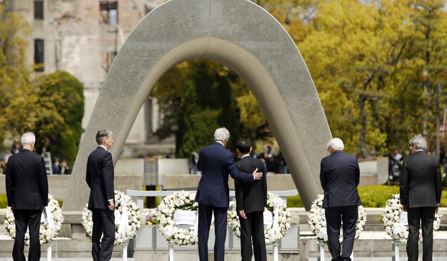 U.S. Secretary of State John Kerry, center left, puts his arm around Japan's Foreign Minister Fumio Kishida after they and fellow G7 foreign ministers laid wreaths at the cenotaph at Hiroshima Peace Memorial Park in Hiroshima, western Japan Monday, April 11, 2016. Also pictured are: Canada's Foreign Minister Stephane Dion, left, Britain's Foreign Minister Philip Hammond, second left, Germany's Foreign Minister Frank-Walter Steinmeier, second right, and Italy's Foreign Minister Paolo Gentiloni, right. (Jonathan Ernst/Pool Photo via AP)