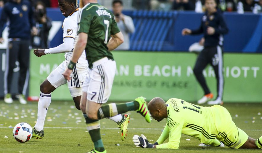 Los Angeles Galaxy forward Gyasi Zardes, left, moves the ball away from Portland Timbers goalkeeper Adam Kwarasey, right, during the first half of an MLS soccer game in Carson, Calif., Sunday April 10, 2016. (AP Photo/Ringo H.W. Chiu)