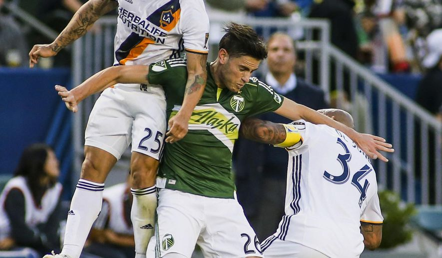 Portland Timbers midfielder Neco Brett, center, battles for heading against Los Angeles Galaxy midfielders Rafael Garcia, left, and Nigel de Jong during the first half of an MLS soccer game in Carson, Calif., Sunday April 10, 2016. (AP Photo/Ringo H.W. Chiu)