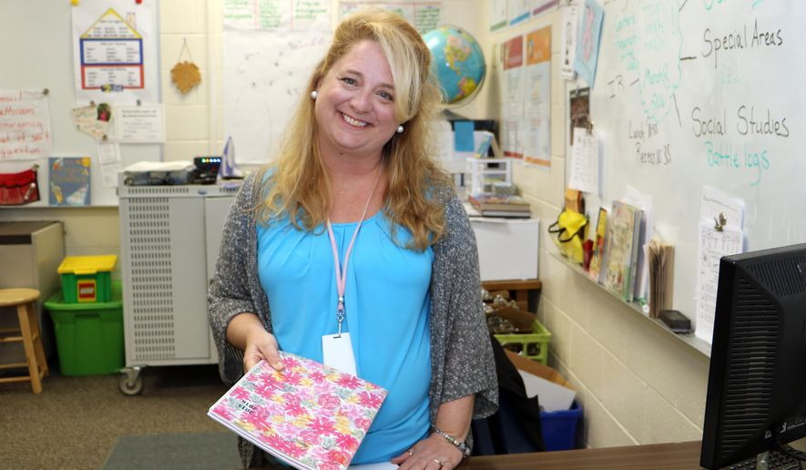 In this March 8 2016 photo, fourth-grade teacher Lori Clarke prepares for her students at Lonnie B. Nelson Elementary in Richland School District 2 in suburban Columbia, S.C. South Carolina's Career Changers loan-forgiveness program nearly covered the cost of Clarke's master's degree in education from the University of South Carolina. After graduating, $45,000 worth of loans were erased over three years of teaching at a high-poverty school in the Columbia area. She now works in a nearby school district. (AP Photo/Seanna M. Adcox)
