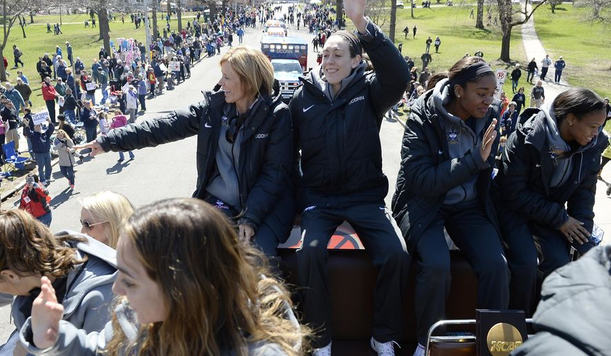 Connecticut associate head coach Chris Dailey, left, and players Breanna Stewart, center, Morgan Tuck, second from right, and Moriah Jefferson, right, wave to fans during a parade celebrating the team's unprecedented fourth consecutive NCAA college basketball tournament championship, Sunday, April 10, 2016, in Hartford, Conn. (AP Photo/Jessica Hill)