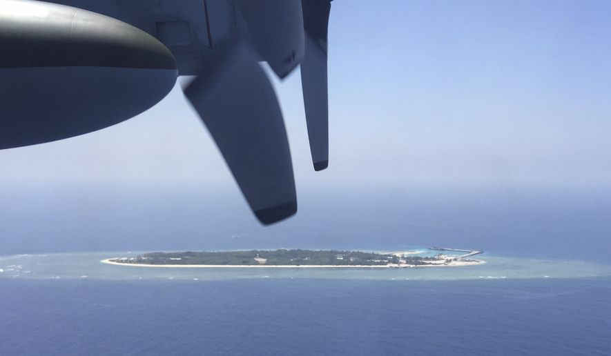 FILE - In this March 23, 2016, file photo, an aerial view is seen from a military plane carrying international journalists of the Taiwan-controlled Taiping island, also known as Itu Aba, in the Spratly archipelago, roughly 1600 kms. (1000 miles) in the South China Sea of southern Taiwan. Tensions in the South China Sea are rising, pitting China against smaller and weaker neighbors who all lay claim to a string of isles, coral reefs and lagoons, rich in fish and potential gas and oil reserves. (AP Photo/Johnson Lai, File)