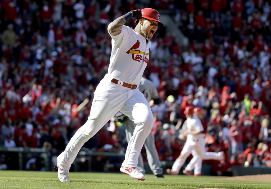 St. Louis Cardinals' Yadier Molina celebrates as he rounds the bases after hitting an RBI double during the third inning of a baseball game against the Milwaukee Brewers on Monday, April 11, 2016, in St. Louis. (AP Photo/Jeff Roberson)