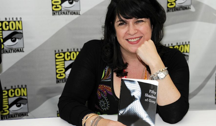 """FILE - In this July 12, 2012, file photo, author E.L. James poses with her book """"Fifty Shades of Grey"""" at a book signing at Comic-Con in San Diego. The top 10 list of """"challenged"""" books at public schools and libraries, released Monday, April 11, 2016, by the American Library Association includes James' best-selling book. (Photo by Denis Poroy/Invision/AP, File)"""