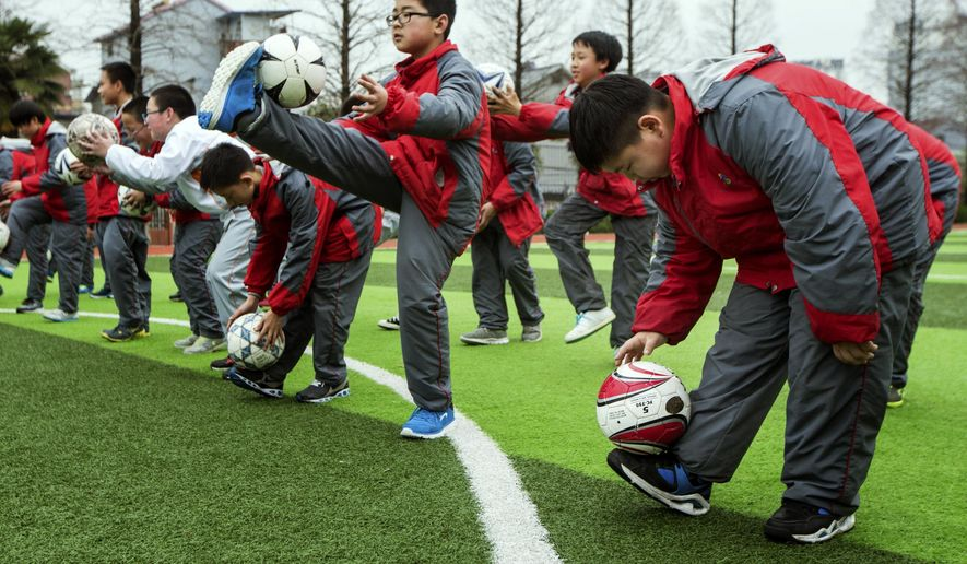 """FILE - In this March 18, 2015 file photo, students take part in soccer class at a middle school in Hangzhou in east China's Zhejiang province. Seeking to close a glaring gap in its international sporting prowess, China has announced an ambitious football development plan that envisions 50 million players joining in the game by the end of the decade and the development of the country into a """"first-rate major footballing power"""" by the middle of the century. (AP Photo/File) CHINA OUT"""