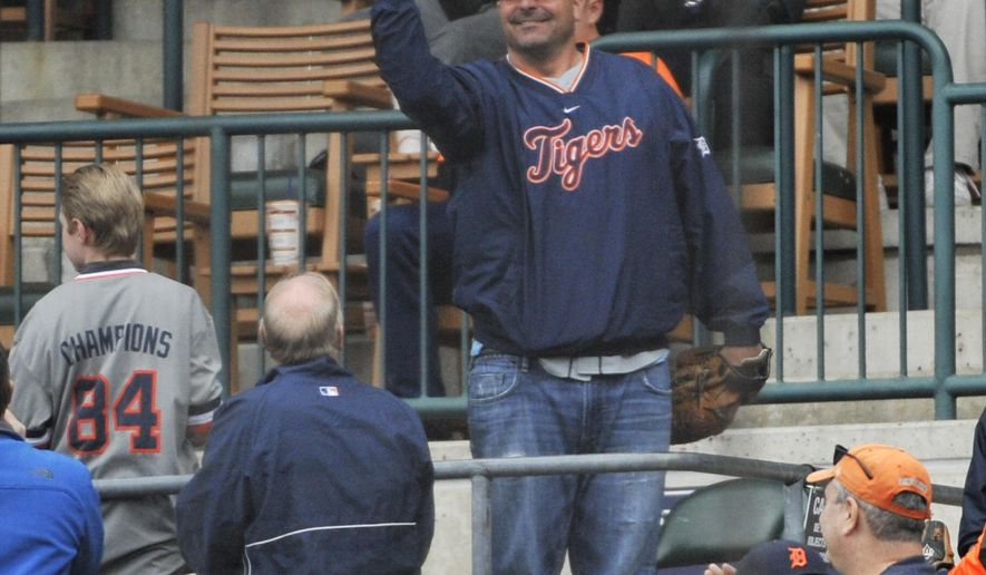 Bill Dugan of Roseville, Mich., shows that he caught five foul balls during the Detroit Tigerss Pittsburgh Pirates at Comerica Park in Detroit on Monday,  April 11, 2016. Dugan, who gave all five to nearby kids, was sitting behind home plate, in an area normally used for fans in wheelchairs. (Robin Buckson/Detroit News via AP)