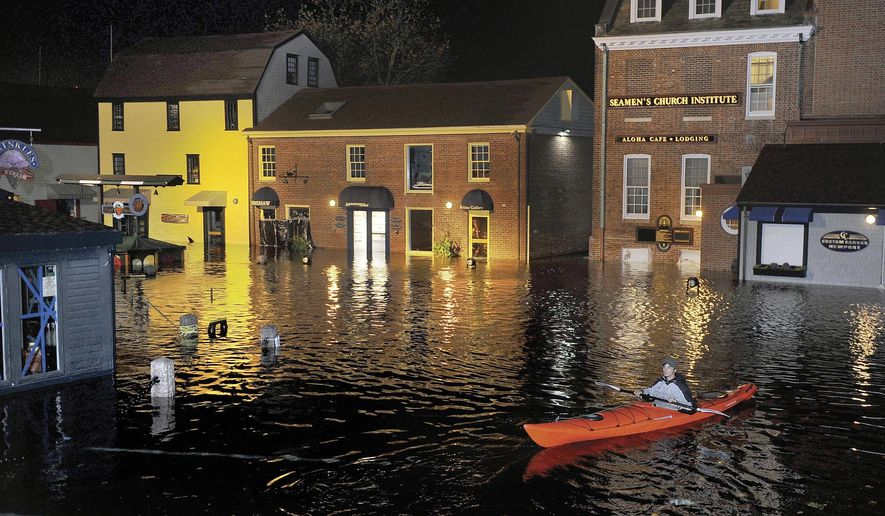 In this October 2012 photo, Jim Davis kayaks through waters flooding Bowen's Wharf after Superstorm Sandy in historic Newport, R.I. With scientists forecasting sea levels to rise by anywhere from several inches to several feet by 2100, historic structures and coastal heritage sites around the world are under threat. A multidisciplinary conference is scheduled to convene in Newport this week to discuss preserving those structures and neighborhoods that could be threatened by rising seas. (Dave Hansen/Newport Daily News via AP) MANDATORY CREDIT