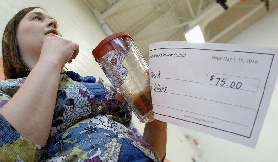 In this March 18, 2016 photo, Cedar Ridge Elementary School teacher Kayleigh Twork holds a check she received from the fundraising efforts of the school's student council in Bloomington, Ill. The fourth- and fifth-graders on the student council awarded $940 to the school this year to purchase things like a new bike rack, learning apps, tablets and books. (David Proeber/The Pantagraph via AP) MANDATORY CREDIT