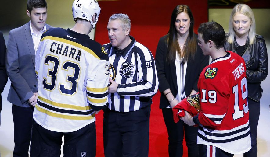 FILE - In this April 3, 2016, file photo, National Hockey League linesman Andy McElman (90), a a 54-year-old resident of Crystal Lake, Ill., surrounded by family receives a signed Boston Bruins sweater from Bruins' Zdeno Chara (33) as Chicago Blackhawks center Jonathan Toews (19) waits to hand him one from the Blackhawks before an NHL hockey game in Chicago. The game was McElman's 1500th and final game in the NHL. (AP Photo/Jeff Haynes, File)