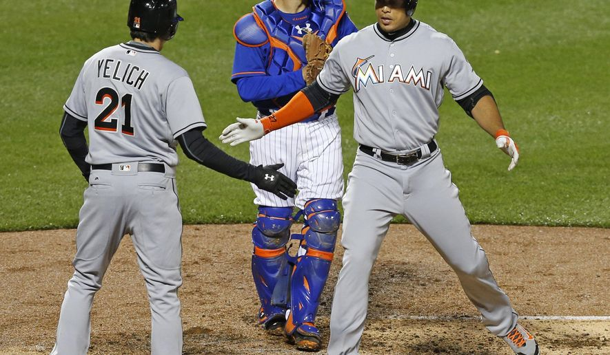 Miami Marlins Giancarlo Stanton greets Christian Yelich (21) after hitting a second-inning, two-run, home run in a baseball game against the New York Mets, Monday, April 11, 2016, in New York. Mets catcher Travis d'Arnaud, center, looks to the outfield. (AP Photo/Kathy Willens)