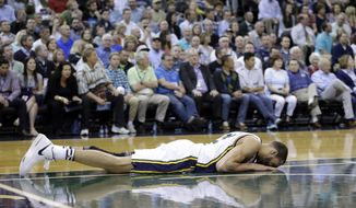 Utah Jazz center Rudy Gobert lays on the floor after injuring his right ankle during the second quarter in an NBA basketball game against the Dallas Mavericks Monday, April 11, 2016, in Salt Lake City. (AP Photo/Rick Bowmer)