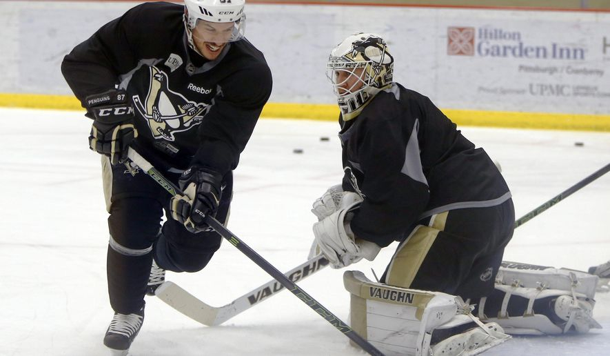 Pittsburgh Penguins' Sidney Crosby, left, shoots against goalie Jeff Zatkoff during a practice session for the NHL hockey playoffs against the New York Rangers, Monday, April 11, 2016, at their practice facility in Cranberry, Pa. (AP Photo/Keith Srakocic)