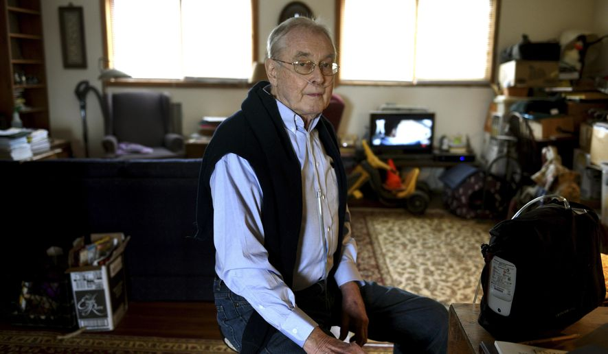 State Rep. Ernie Bridge, R-Unity, poses for a photo at his home on April 8, 2016, in Unity, N.H. Bridge has developed a lung problem which requires him to use an oxygen concentrator, seen at right. Bridge has been told not to bring his portable oxygen concentrator with him to the Statehouse because it creates a safety hazard. (Jennifer Hauck/The Valley News via AP))