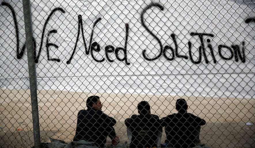 Migrants sit below a banner outside a former Olympic indoor stadium in Faliro, southern Athens        Associated Press photo