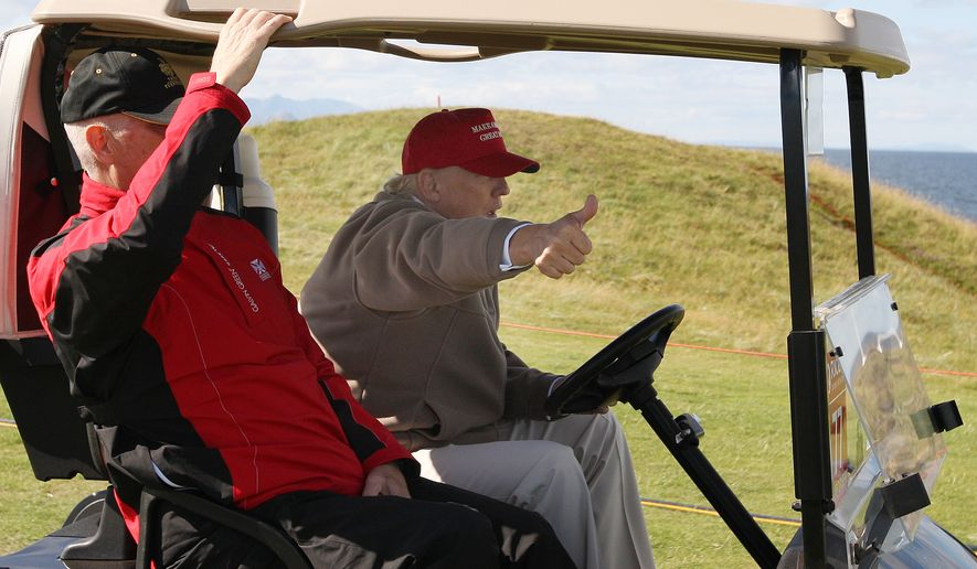 U.S. Presidential contender Donald Trump, right, gestures to the media as he drives a buggy on the first day of the Women's British Open golf championship at the Turnberry golf course in Turnberry, Scotland, Thursday, July 30, 2015. Trump turned a brief trip to a golf tournament in Scotland into an extension of his presidential campaign trail when he attended the Women's British Open at his plush Turnberry resort on Thursday. (AP Photo/Scott Heppell)