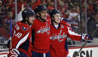 Washington Capitals center Marcus Johansson (90), from Sweden, Washington Capitals left wing Alex Ovechkin (8), from Russia, and Washington Capitals right wing T.J. Oshie (77) celebrate Ovechkin's goal in the first period of an NHL hockey game against the New York Islanders, Tuesday, April 5, 2016, in Washington. (AP Photo/Alex Brandon)