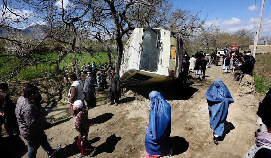 In this Monday, April 11, 2016, file, photo, Afghan women walk past a damaged bus after a roadside bomb explosion on the outskirts of Kabul, Afghanistan, The Afghan Taliban have announced the start of their warm-weather fighting season, an annual declaration that marks the launch of a summer of violence. (AP Photo/Rahmat Gul)