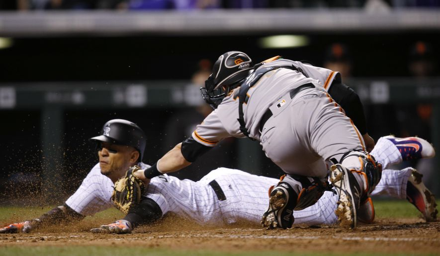 San Francisco Giants catcher Trevor Brown, front, tagsout Colorado Rockies' Carlos Gonzalez at home plate as he tried to score on a bloop single by Nolan Arenado, to end the fifth inning of a baseball game Tuesday, April 12, 2016, in Denver. The Giants won 7-2. (AP Photo/David Zalubowski)