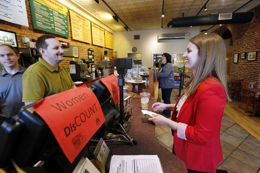 Molly Kepner, right, smiles after hearing the news of her discount from Tom Grover at The Works Bakery Cafe, Tuesday, April 12, 2016 in Concord, N.H. The New Hampshire bakery chain gave women a break in honor of Equal Pay Day charging them 79 percent of their bill. (AP Photo/Jim Cole)