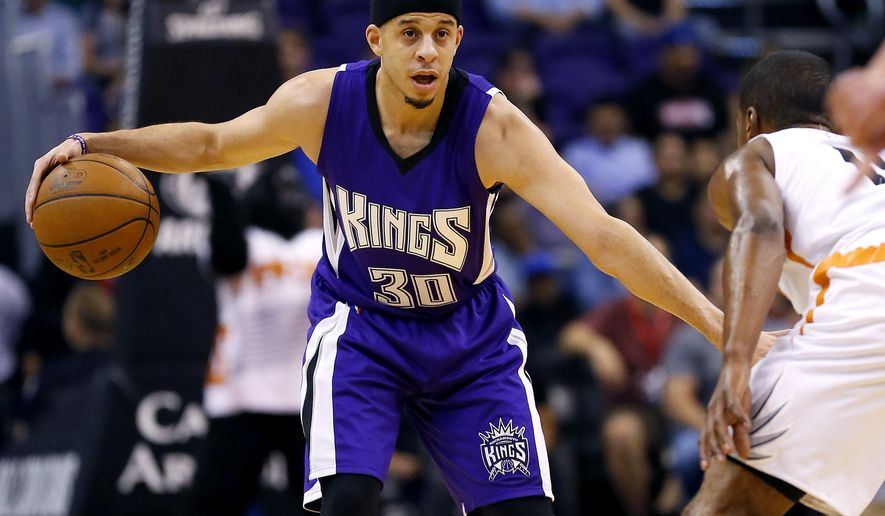 Sacramento Kings guard Seth Curry (30) looks to pass as Phoenix Suns guard Ronnie Price defends during the first half of an NBA basketball game, Monday, April 11, 2016, in Phoenix. (AP Photo/Matt York)