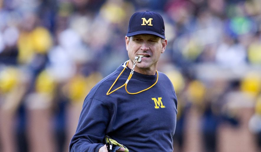 Michigan head coach Jim Harbaugh holds a whistle between his teeth as he walks the field between downs in the NCAA college football team's annual Spring Game at Michigan Stadium in Ann Arbor, Mich., Friday, April 1, 2016. (AP Photo/Tony Ding)