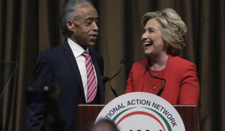 The Rev. Al Sharpton joins Democratic presidential candidate Hillary Clinton at the podium after her speech at the 25th annual National Action Network convention in New York last week. (Associated Press)