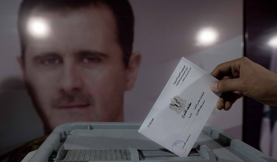 A Syrian man casts his vote at a polling station during the parliamentary election in Damascus, Syria, Wednesday, April 13, 2016. Polling stations opened in government-held parts of Syria where a new 250-member parliament will be elected. (AP Photo/Hassan Ammar)