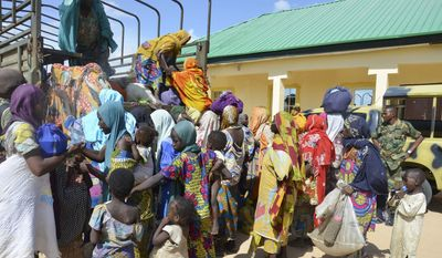 In this July 30, 2015, file photo, women and children rescued by Nigerian soldiers from the Islamic extremist group Boko Haram in the northeast of Nigeria arrive at the military office in Maiduguri, Nigeria. A video appearing to show proof of life of some of Nigeria's kidnapped Chibok girls was aired, Wednesday, April 13, 2016, along with images of tearful parents recognizing their daughters, unheard of since the mass abduction by the Boko Haram two years ago. (AP Photo/Jossy Ola, File)