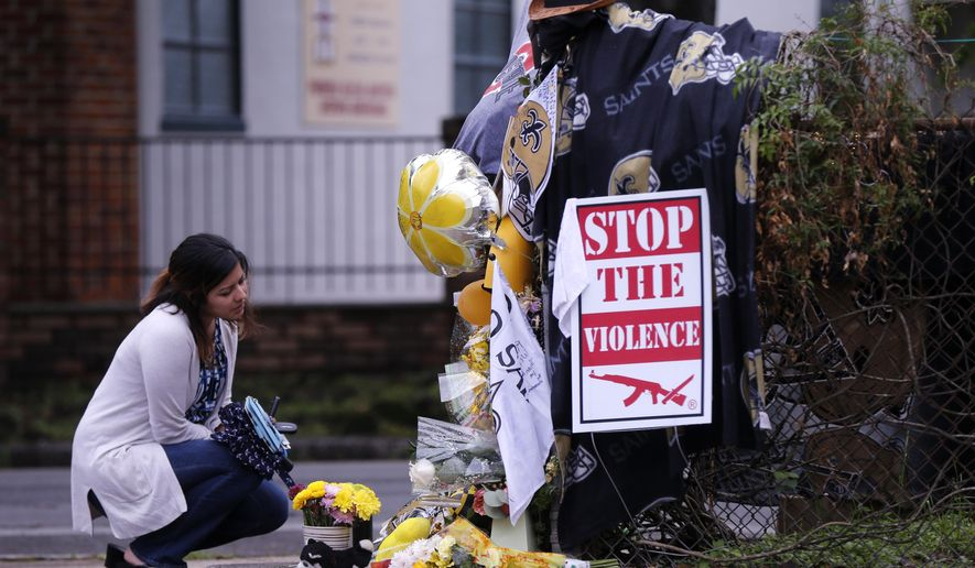 Gabriella Ortiz, of New Orleans, pauses at a makeshift memorial in New Orleans, Tuesday, April 12, 2016, near the spot where former New Orleans Saints defensive end Will Smith was shot and killed, and his wife wounded by gunfire, after a traffic accident last Saturday. (AP Photo/Gerald Herbert)