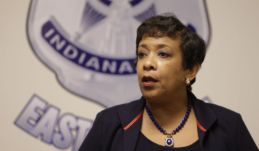 Attorney General Loretta E. Lynch talks with police officers in Indianapolis as part of her national Community Policing Tour, Wednesday, April 13, 2016. (AP Photo/Michael Conroy)