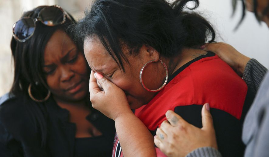 In this Tuesday, April 12, 2016 photo, family members comfort Tambrasha Hudson as she cries over the shooting death of her 16-year-old son, Pierre Loury, by a Chicago police officer the night before. Chicago police say Loury was shot and killed during a chase after the teen turned and pointed a gun. Hudson denied her son had a gun. (Jose M. Osorio/Chicago Tribune via AP) MANDATORY CREDIT CHICAGO TRIBUNE; CHICAGO SUN-TIMES OUT; DAILY HERALD OUT; NORTHWEST HERALD OUT; THE HERALD-NEWS OUT; DAILY CHRONICLE OUT; THE TIMES OF NORTHWEST INDIANA OUT; TV OUT; MAGS OUT; NO SALES