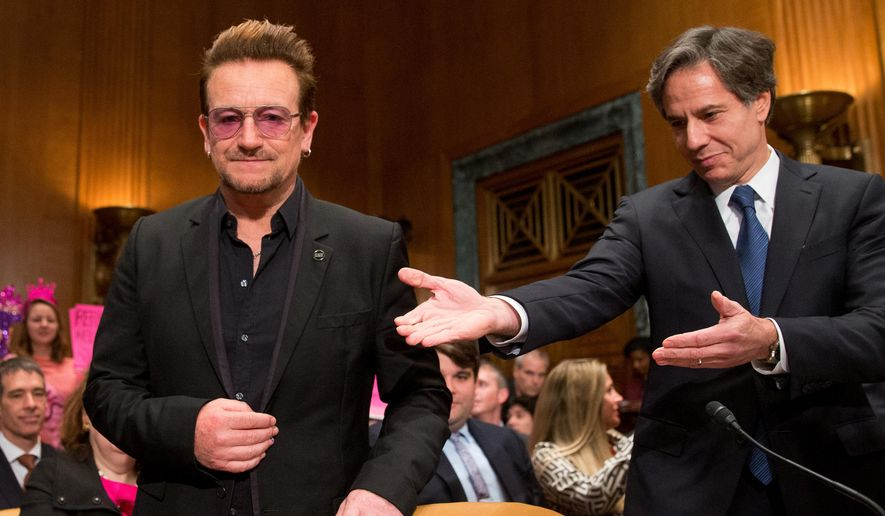 Irish rock star and activist Bono, accompanied by U.S. Deputy Secretary of State Tony Blinken, right, arrives on Capitol Hill in Washington, Tuesday, April 12, 2016, to testify before the Senate State, Foreign Operations, and Related Programs subcommittee hearing on the causes and consequences of violent extremists, and the role of foreign assistance. (AP Photo/Andrew Harnik)