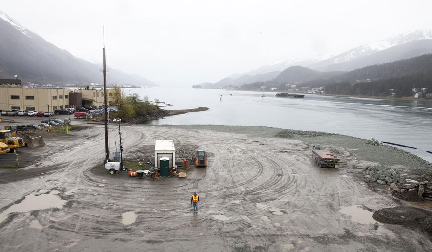 CORRECTS DATE FROM WEDNESDAY TO TUESDAY- A city worker walks along a site that will soon host a life-sized whale sculpture and bridge park project along the Gastineau Channel, Tuesday, April 12, 2016, in Juneau, Alaska. The city is being sued by a industry representative for 12 cruise lines which alleges that the city is misspending funds from a per-passenger tax on the whale project and others which do not directly benefit cruise passengers.  (AP Photo/Rashah McChesney)