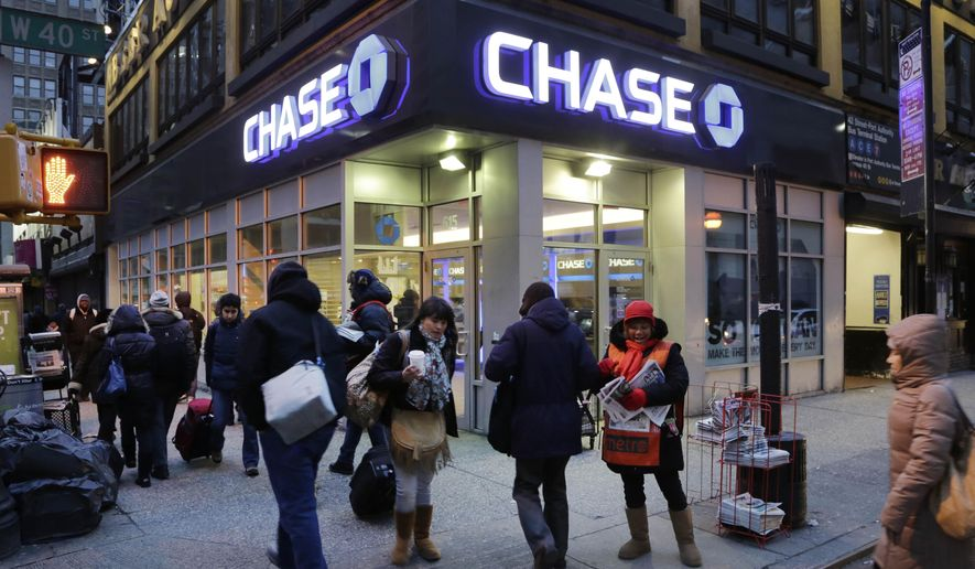 FILE - In this Jan. 14, 2015, file photo, people walk past a branch of Chase Bank, in New York. JPMorgan Chase & Co. (JPM) on Wednesday, April 13, 2016, reported first-quarter earnings.  (AP Photo/Mark Lennihan, File)