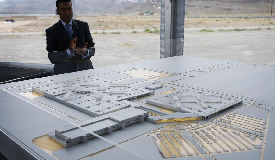 Nevada Gov. Brian Sandoval looks at a model for a Faraday Future factory, Wednesday, April 13, 2016, in North Las Vegas, Nev. The upstart electric car company held an event to mark the start of construction at a Las Vegas-area production plant toward which Nevada had pledged up to $335 million worth of incentives. (AP Photo/John Locher)