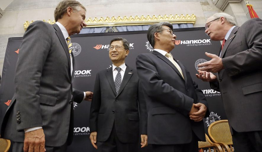 Tennessee Gov. Bill Haslam, left, talks with S. H. John Sun, vice chairman and CEO of Hankook Tire Wednesday, April 13, 2016, in Nashville, Tenn., after it was announced that Hankook is relocating its North American headquarters from New Jersey to Tennessee. Ralph Schulz, right, president of the Nashville Chamber of Commerce, talks with Hee Se Ahn, president of Hankook Tire America Corp. (AP Photo/Mark Humphrey)