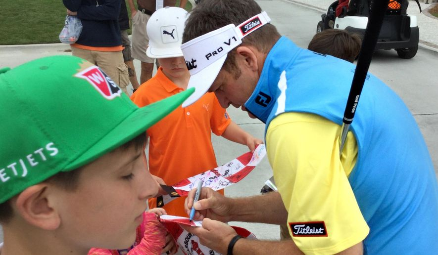 In this photo taken Tuesday, April 12, 2016, Jason Bohn signs autographs near the putting green at Harbour Town Golf Links in Sea Pines on Hilton Head Island, S.C., after his practice round inthe RBC Heritage golf tournament. Bohn is playing his first PGA Tour event since suffering a heart attack in February. (Stephen Fastenau/The Island Packet via AP) MANDATORY CREDIT