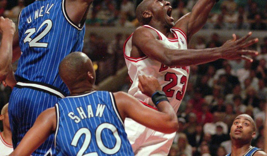 FILE - In this May 21, 1996, file photo, Chicago Bulls' Michael Jordan drives past Orlando Magic's Shaquille O'Neal (32) as Brian Shaw (20) watches during an NBA Eastern Conference finals basketball game in Chicago. Absent a time machine, we'll never know whether this season's Golden State Warriors are as good or better than the 1995-96 Bulls. But we do know they're neck-and-neck.(AP Photo/Michael Conroy, File)